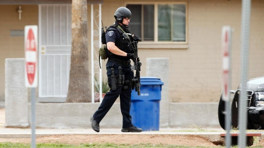 An officer stands guard outside Adams Elementary School while searching for a gunman on Wednesday, March 18, 2015, in Mesa, Ariz. A gunman in a rampage that included a motel shooting, a carjacking and a home invasion ended with his arrest at a nearby apartment in suburban Phoenix. (AP Photo/The Arizona Republic, Rob Schumacher)
