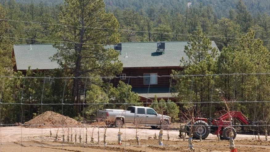 FILE - In this April 22, 2008 file photo, a log-cabin-style home is among the buildings on the Fundamentalist Church of Jesus Christ of Latter Day Saints' compound that has nearly 50,000 square feet of residential space near Pringle, S.D. The sect has applied to the state of South Dakota to double the amount of water it can take from an aquifer prompting concern by neighbors and law enforcement about a possible influx of members who are being displaced from a compound on the Utah- Arizona border. (AP Photo/Mike Stewart, File)