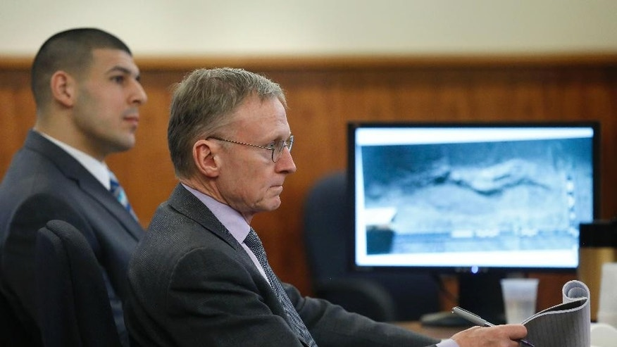 Former New England Patriots football player Aaron Hernandez, left, sits with defense attorney Charles Rankin, center, as an image of a footprint is displayed on a monitor during Hernandez's murder trial, Thursday, March 19, 2015, in Fall River, Mass. Hernandez is charged with killing semiprofessional football player Odin Lloyd. Police say the footprint was found near Lloyd's body and is consistent with the shoes Hernandez was seen wearing near the time of the killing. (AP Photo/Steven Senne, Pool)