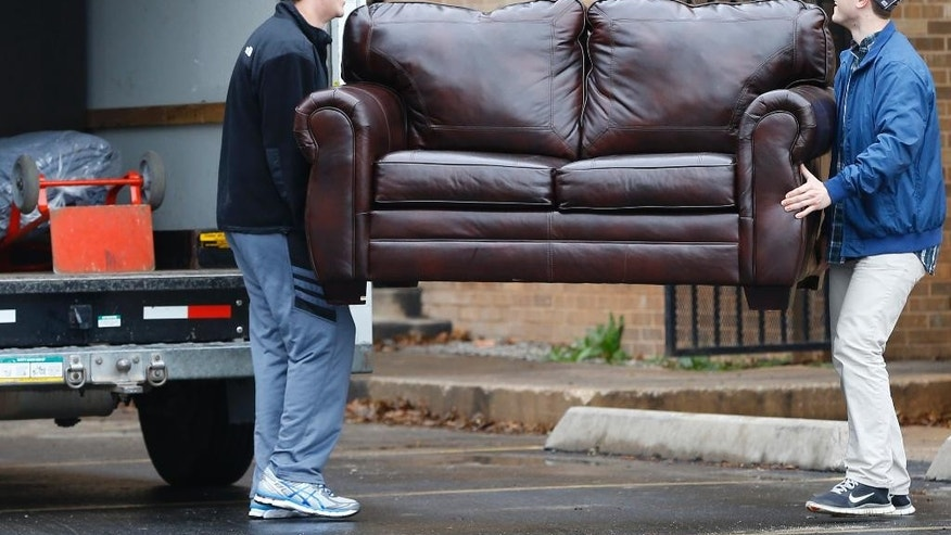 File-This March 10, 2015, file photo shows two men loading a couch from the now closed University of Oklahoma's Sigma Alpha Epsilon fraternity house into a moving truck, in Norman, Okla. Fraternities dominate social life at many American universities, but lately these organizations of male college students have been receiving unwanted attention for their bad behavior. At the University of Oklahoma, one prominent fraternity was shut down after members were caught on video performing a racist chant. (AP Photo/Sue Ogrocki, File)