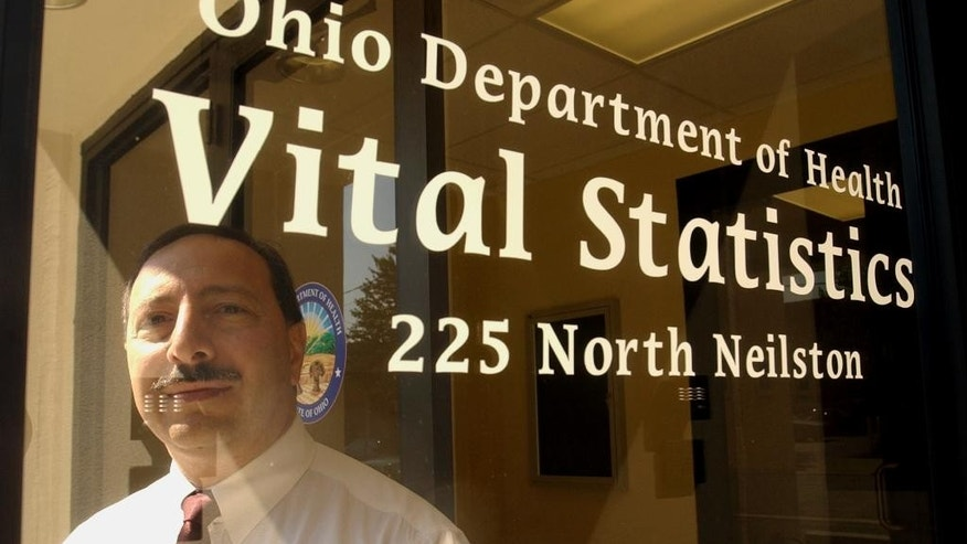 FILE-  Mark Kassouf, chief fraud officer for the Ohio Department of Health stands at the entrance to the Ohio Department of Vital Statistics in Columbus, Ohio, in this Sept. 1, 2004 file photo. Beginning Friday, March 20, 2015 individuals who were adopted between January 1, 1964, and September 18, 1996, can request their adoption files and birth certificates from the Ohio Department of Health.  (AP Photo/Tony Dejak, File)