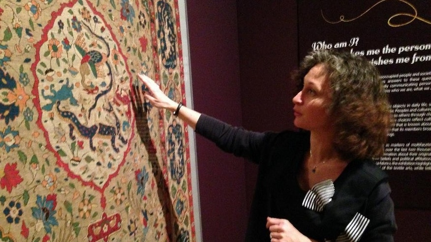 This photo taken March 16, 2015 shows senior curator Sumru Belger Krody discussing the imagery depicted in an Asian textile piece at the The George Washington University Museum and The Textile Museum  in Washington. The George Washington University Museum and The Textile Museum open a new building, featuring textiles from five continents spanning 5,000 years. Two other exhibits feature the planning of the nation's capital and the impact of the Civil War.  (AP Photo/Brett Zongker)