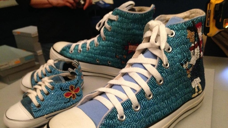 This photo taken March 16, 2015 shows Converse All-Star sneakers embroidered with Native American beads, made in 2003, are on loan from the Indian Arts Research Center to The George Washington University Museum and Textile Museum in Washington. Beadwork is a textile art that celebrates native heritage. The George Washington University Museum and The Textile Museum open a new building, featuring textiles from five continents spanning 5,000 years. Two other exhibits feature the planning of the nation's capital and the impact of the Civil War.  (AP Photo/Brett Zongker)