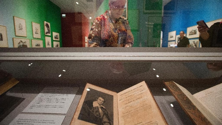 "In this March 17, 2015 photo, Rebecca Smith, Head, Special Collections at HistoryMiami in Miami, opens a display case housing papers about the Audubon collection.  A new HistoryMiami exhibit shows every image printed for Audubon's masterpiece, ""The Birds of America. ""(AP Photo/J Pat Carter)"
