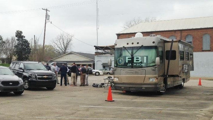 FBI agents meet outside a portable command post in Port Gibson, Miss., as they continue their investigation into the circumstances surrounding the hanging death of Otis Byrd, an ex-convict reported missing by his family more than two weeks ago, Friday, March 20, 2015. Byrd lived just 200 yards from the spot in a wooded area off a dirt road that ran behind his house, where his hanged body was found Thursday, by state wildlife officers called in to help with the search for him. (AP Photo/Jeff Amy)