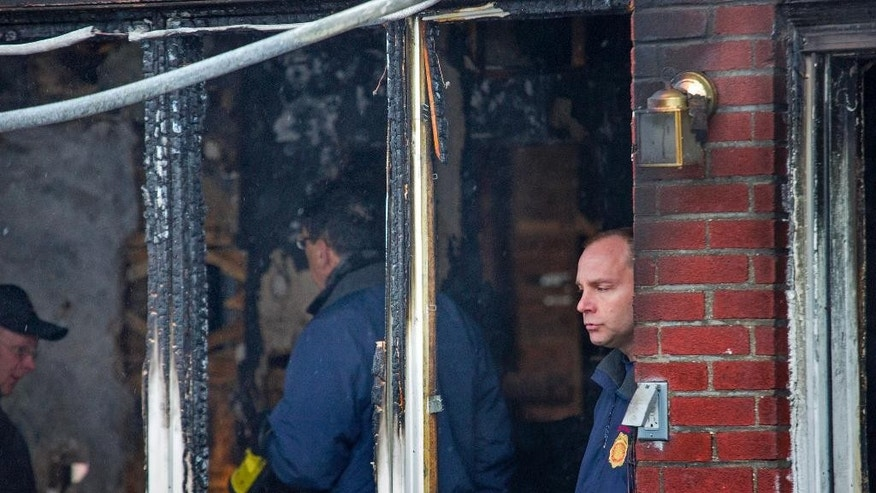 New York's Fire Commissioner Daniel Nigro, center, and others look over the remains of a home after a fire in the Brooklyn borough of New York,  Saturday, March 21, 2015. The fire raged through the residence early Saturday, killing seven children and leaving two other people in critical condition, authorities said. (AP Photo/Craig Ruttle)