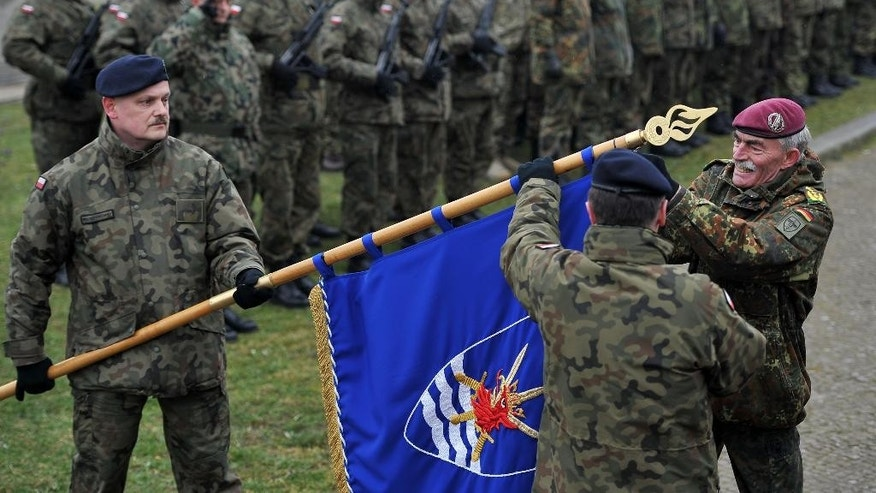 Gen. Hans-Lothar Domroese from Germany, right, decorates the flag of the NATO Multinational Corps Northeast during a ceremony marking the transition from the forces of lower readiness headquarters to the high readiness forces headquarters in Szczecin, Poland, Saturday, March 21, 2015. (AP Photo/Lukasz Szelemej)