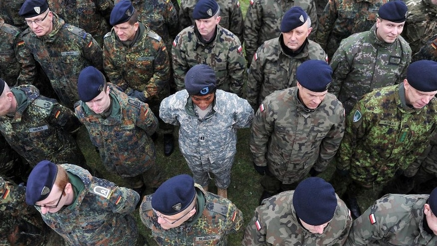 Soldiers from the Multinational Corps Northeast attend a ceremony marking the transition from the forces of lower readiness headquarters to the high readiness forces headquarters in Szczecin, Poland, Saturday, March 21, 2015. (AP Photo/Lukasz Szelemej)