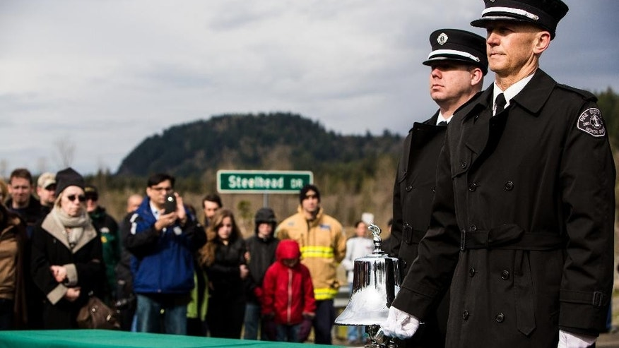 Honor Guard members ring a silver bell for each victim as fire department officials read off the names of victims who lost their lives in the Oso slide, as photographed Sunday, March 22, 2015, on the one year anniversary of  the tragedy that left 43 dead in the town of Oso, Washington. (AP Photo/seattlepi.com, Jordan Stead)