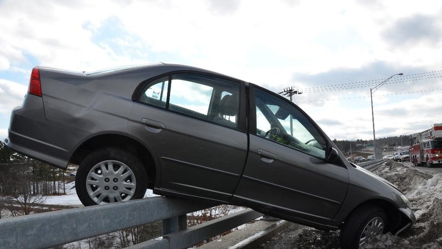 In this Saturday, March 21, 2015 photo provided by the Hudson, N.H. Fire Department, a Honda Accord rests on a guardrail on the Sagamore Bridge over the Merrimack River in Nashua, N.H. Colin Malone, 17, was driving eastbound when he lost control of the vehicle and hit a snowbank, sending the car airborne and onto the guardrail. Malone was issued a citation for failing to keep his vehicle within roadway markings, but escaped unscathed. (AP Photo/ Hudson, N.H. Fire Department, David S. Morin)
