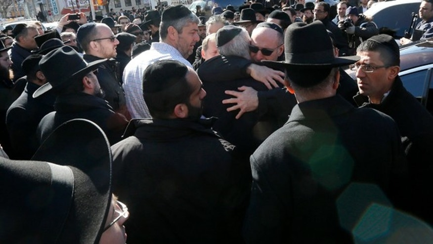 March 22, 2015: Mourners embrace each other after funeral services for seven siblings killed in a house fire in the Brooklyn borough of New York. (AP Photo/Julio Cortez)
