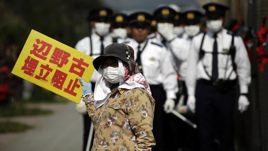"Japanese police officers stand guard as a protester against the relocation of U.S. Marine Corps Air Station Futenma, as protesters stage a rally outside Camp Schwab, an American base near a planned relocation site, in Nago, Okinawa Prefecture, Monday, March 23, 2015. The governor of the southern Japanese island of Okinawa has ordered a Defense Ministry branch to suspend all work at the site where a key U.S. military air base is to be relocated. The U.S. and Japan reached the relocation agreement in 1996. The banner reads: ""Henoko, Block reclamation."" (AP Photo/ Eugene Hoshiko)"