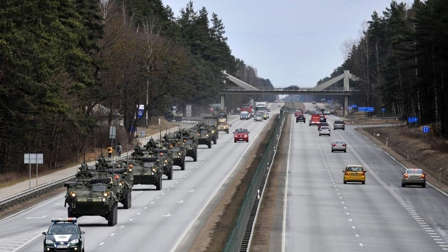 Stryker vehicles of the US Army's 2nd Cavalry Regiment roll the highway, during ''Dragoon Ride'' military exercise,  in Riga, Latvia, Sunday, March 22, 2015. The troops began the trek on March 21, and will travel through Latvia, The Czech Republic and onto Germany by April 1 in an exercise designed to reinforce America's allies. (AP Photo/Oksana Dzadan)
