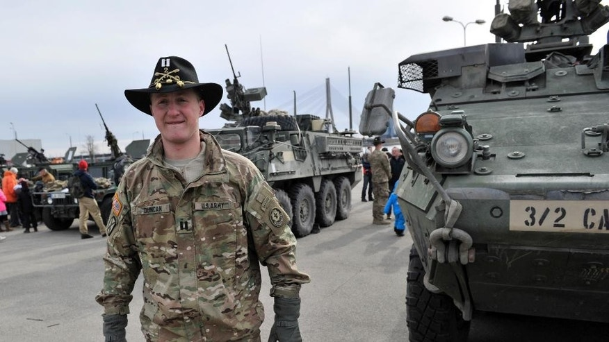 US Army's Captain Michael Duncan smiles in front of a Stryker vehicle of the US Army's 2nd Cavalry Regiment, during the ''Dragoon Ride'' military exercise,  in Riga, Latvia, Sunday, March 22, 2015. The troops began the trek on March 21, and will travel through Latvia, The Czech Republic and onto Germany by April 1 in an exercise designed to reinforce America's allies. (AP Photo/Oksana Dzadan)