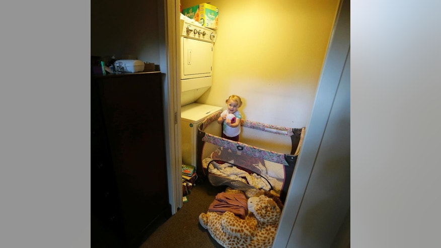 In this March 3, 2015 photo, Elea Kelly, 2, the daughter of Jenny and Michael Kelly, stands in her crib, which is housed in a laundry room off of her parents' bedroom in their loft apartment in Seattle's downtown Pioneer Square neighborhood. A small but growing number of parents are bucking the trend of moving to suburbs when they have children, and they're pushing cities to be more welcoming to families. (AP Photo/Ted S. Warren)