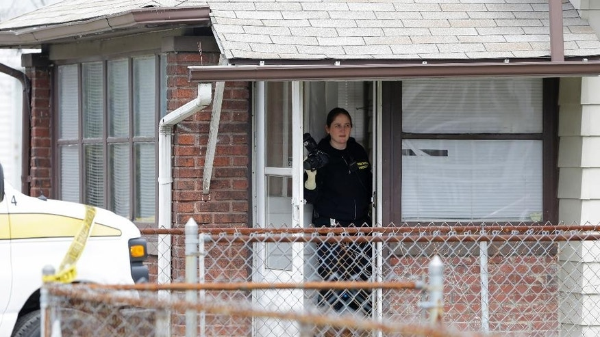 Indianapolis Crime Lab personnel investigate a scene involving four homicide victims at a house in Indianapolis, Tuesday, March 24, 2015. Indianapolis Police Chief Rick Hite says three women and a man have been shot to death in the home. Hite says the shootings don't appear random and likely occurred Tuesday morning. (AP Photo/Michael Conroy)