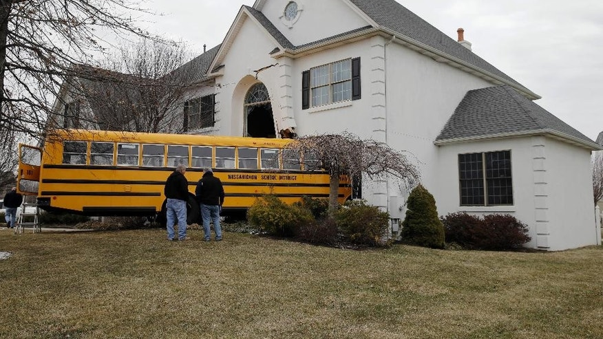 Men inspect a school bus that crashed into a home Tuesday morning, March 24, 2015, in Blue Bell, Pa. Officials say nine students from St. Helena School were aboard, but none were injured, when the bus slammed into the suburban Philadelphia home around 7:45 a.m. Tuesday. Officials say the bus driver was taken to Abington Hospital. A person inside the home was not injured. (AP Photo/Matt Rourke)