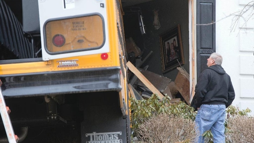 A man inspects a school bus that crashed into a home Tuesday morning, March 24, 2015, in Blue Bell, Pa. Officials say nine students from St. Helena School were aboard, but none were injured, when the bus slammed into the suburban Philadelphia home around 7:45 a.m. Tuesday. Officials say the bus driver was taken to Abington Hospital. A person inside the home was not injured. (AP Photo/Matt Rourke)