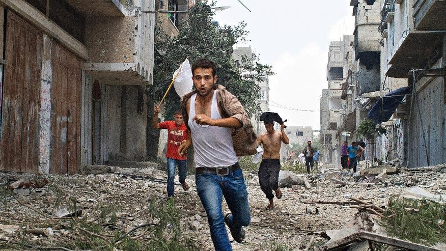 This handout photo provided by the International Women's Media Foundation, taken by Heidi Levine on July 20, 2014, shows Palestinian men running in the Shejaia neighborhood of Gaza City, which was heavily shelled by Israel during fighting. A women's media group will honor freelance photographer Heidi Levine as the inaugural winner of an award for courage named for Associated Press photographer Anja Niedringhaus, who was killed on assignment in Afghanistan. The International Women's Media Foundation in Washington announced Tuesday that Levine will be awarded the Anja Niedringhaus Courage in Photojournalism Award. Levine is an American and is based in Jerusalem. (AP Photo/Heidi Levine, International Women's Media Foundation)