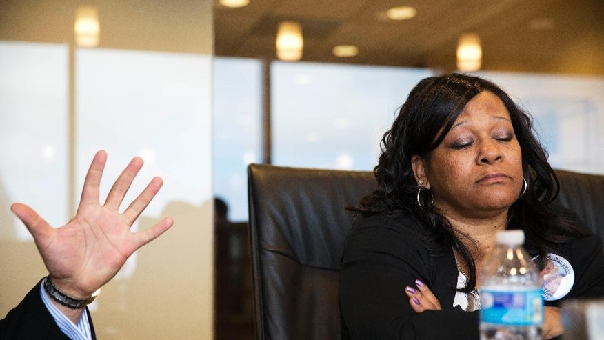 Carolyn Baylor Giummo, right, the mother of Anthony Hill, a naked, mentally ill man who was fatally shot by a police officer, listens as attorney Christopher Chestnut gestures while speaking during an interview, Wednesday, March 25, 2015, in Atlanta. Chestnut says witness statements suggest DeKalb County police officer Robert Olsen could have retreated before fatally shooting Hill, 26, on March 9 while responding to a call reporting a suspicious person knocking on doors and crawling naked on the ground. (AP Photo/David Goldman)