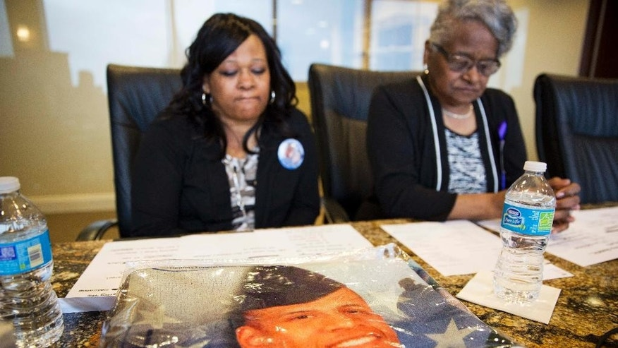 A blanket decorated with the portrait of Anthony Hill rests on a table as Hill's mother Carolyn Baylor Giummo, left, and grandmother Theola Baylor, sit for an interview Wednesday, March 25, 2015, in Atlanta. An attorney for Hill's family, Christopher Chestnut, says witness statements suggest DeKalb County police officer Robert Olsen could have retreated before fatally shooting Hill, 26, on March 9 while responding to a call reporting a suspicious person knocking on doors and crawling naked on the ground. (AP Photo/David Goldman)
