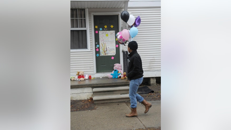 A woman walks past notes left on the door at a town home in Detroit, Wednesday, March 25, 2015, where two bodies were found. A Detroit mother was arrested Tuesday after the frozen bodies of a boy and girl were found in a deep freezer in the family's home, police said. Court officers found the children's bodies while carrying out an eviction order at the 3-bedroom home in the apartment complex. (AP Photo/Detroit News, Clarence Tabb Jr.)  DETROIT FREE PRESS OUT; HUFFINGTON POST OUT; MANDATORY CREDIT
