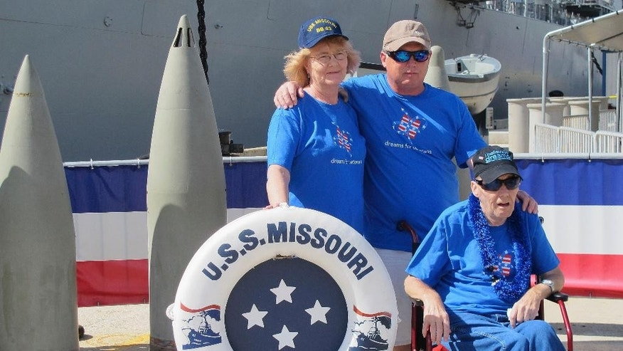 Joseph Hooker, a terminally ill Vietnam veteran, bottom right, poses for a souvenir photo in front of the battleship USS Missouri with his brother Lester Hooker, top right, and sister-in-law Rennie Hooker while visiting Pearl Harbor, Hawaii, Wednesday, March 25, 2015. Joseph Hooker's longtime dream to visit Pearl Harbor has come true. The Dream Foundation arranged for the 63-year-old to travel from his home in Essex, Maryland, to Hawaii. (AP Photo/Jennifer Sinco Kelleher)