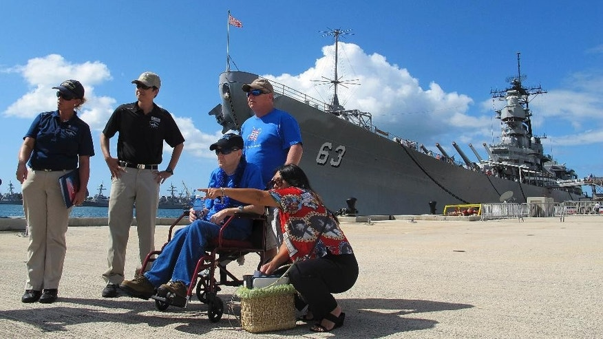 Joseph Hooker, a terminally ill Vietnam veteran, sits in a wheelchair as his brother Lester Hooker stands behind him as they listen as Joint Base Pearl Harbor-Hickam volunteer historian Jessie Higa, bottom center, describes the USS Arizona memorial with tour guides Cathy Gabriel, left, and Frank Clay and the battleship USS Missouri in the background in Pearl Harbor, Hawaii, Wednesday, March 25, 2015. Joseph Hooker's longtime dream to visit Pearl Harbor has come true. The Dream Foundation arranged for the 63-year-old to travel from his home in Essex, Maryland, to Hawaii. (AP Photo/Jennifer Sinco Kelleher)