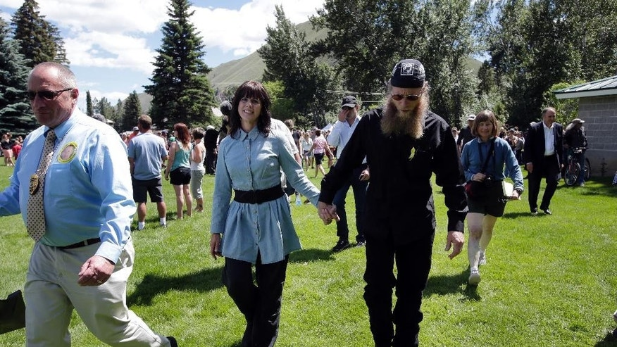 "FILE- In this June 22, 2013 file photo, U.S. Army Sgt. Bowe Bergdahl's parents Jani Bergdahl, center left, and her husband, Bob, walk during a ""Bring Bowe Back"" celebration held to honor Sgt. Bergdahl in Hailey, Idaho. A U.S. official says Bowe Bergdahl, who abandoned his post in Afghanistan and was held by the Taliban for five years, will be court martialed on charges of desertion and avoiding military service. (AP Photo/Jae C. Hong, File)"