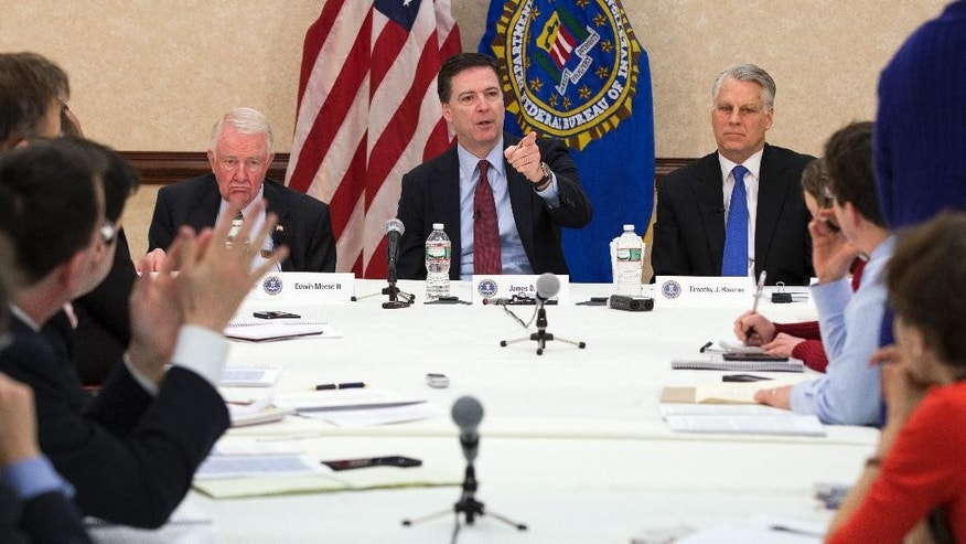 FBI director James Comey, center, flanked by former Attorney General Edwin Meese, left, and former Indiana Rep. Tim Roemer, gestures during a news conference at FBI headquarters in Washington, Wednesday, March 25, 2015, after the release of the 9/11 Review Commission report. The report says the FBI must speed up the pace of its improvements to deal with the evolving terrorist threat around the world. The group was established last year to measure how well the FBI had followed an earlier set of recommendations in the aftermath of the Sept. 11 terror attacks. (AP Photo/ Evan Vucci)