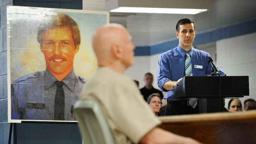 Mac Holcomb, son of Officer Robert Holcomb, looks over inmate Gary Castonguay during a hearing inside MacDougall-Walker Correctional Institution, Wednesday, March 25, 2015, in Suffield, Conn. Castonguay, is serving a sentence of 25 years to life in prison for the shooting of Holcomb during a burglary.  A parole board that ruled Castonguay,  who killed Holcomb in 1977 could go free,  rescinded that decision Wednesday after an outcry from the victim's family and prosecutors. (AP Photo/Jessica Hill)