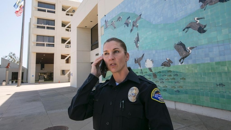 A police officer stands at the location where a missing woman was found in Huntington Beach, Calif., on Wednesday, March 25, 2015.  Denise Huskins whose boyfriend reported that intruders abducted her from their San Francisco Bay Area home and held her for ransom was found safe Wednesday at her father's Southern California home, police said. (AP Photo/Damian Dovarganes)