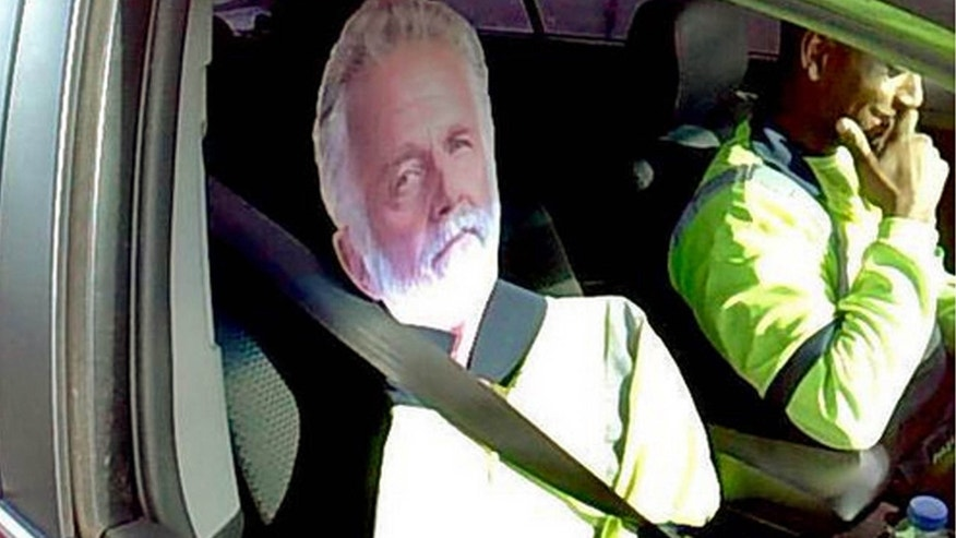"March 23, 2015: Washington State Patrol Trooper Tony Brock shows a cardboard cutout of the ""The Most Interesting Man In The World,"" otherwise known as actor Jonathan Goldsmith, of Dos Equis beer TV commercial fame, strapped to the passenter seat of a driver who tried to use the image to qualify to drive the carpool lane on Interstate 5 near Fife, Wash."