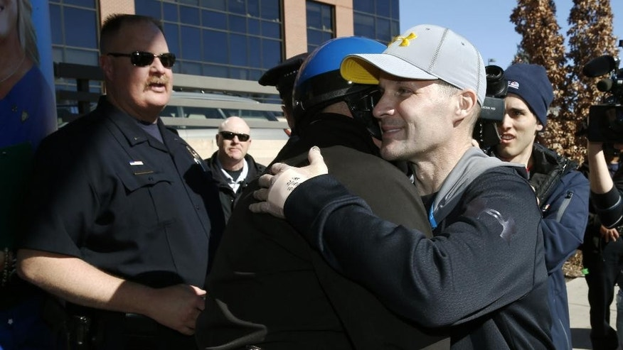 File - In this Feb. 18, 2015 file photo, Denver Police Department officer John Adsit, right, hugs fellow officers as Adsit leaves Porter Adventist Hospital, in south Denver after recovering from injuries suffered when hit by a car while securing a parade route for protesters on Dec. 3, 2014.   Denver Police announced Wednesday, March 25, 2015 that 42-year-old Christopher Booker was arrested on charges of assault, forgery and attempting to influence a public servant. (AP Photo/David Zalubowski, file)
