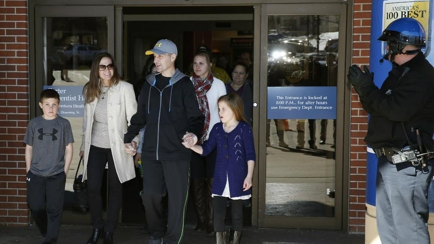 File - In this Feb. 18, 2015 file photo, Denver Police Department officer John Adsit, third from left, is flanked by his family as he leaves Porter Adventist Hospital, in south Denver after recovering from injuries suffered when hit by a car while securing a parade route for protesters on Dec. 3, 2014.  . Denver Police announced Wednesday, March 25, 2015 that 42-year-old Christopher Booker was arrested for the incident on charges of assault, forgery and attempting to influence a public servant. (AP Photo/David Zalubowski, file)
