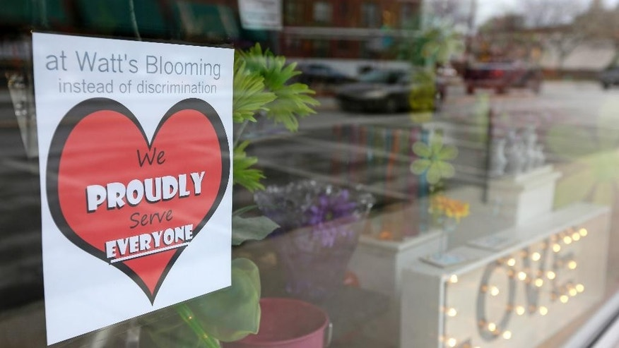A window sign on a downtown Indianapolis florist, Wednesday, March 25, 2015, shows it's objection to the Religious Freedom bill passed by the Indiana legislature. Organizers of a major gamers' convention and a large church gathering say they're considering moving events from Indianapolis over a bill that critics say could legalize discrimination against gays. (AP Photo/Michael Conroy)
