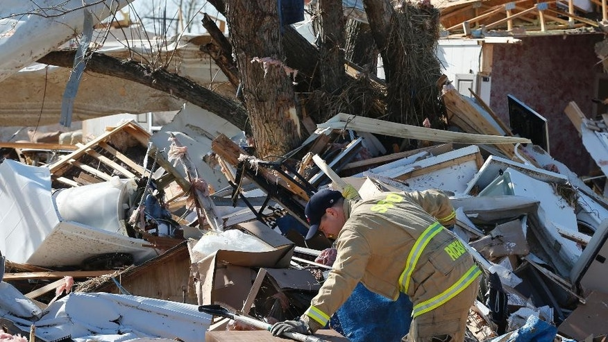 Dugan Ridenour of the Sand Springs fire department digs through rubble in the tornado-damaged River Oaks Estates mobile home park in Sand Springs, Okla., Thursday, March 26, 2015. Mary Fallin has declared a state of emergency for 25 Oklahoma counties after powerful storms rumbled across the state Wednesday evening and produced tornadoes and flat-line winds that led to one death, numerous injuries and widespread damage. (AP Photo/Sue Ogrocki)