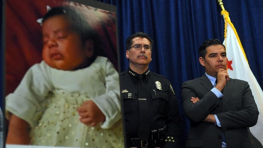 Long Beach Police Chief Robert Luna, left, and Mayor Robert Garcia stand during a news conference in Long Beach, Calif., Wednesday, March 25, 2015. Southern California authorities have arrested four people in a plot to kidnap two newborn babies. The plot ended with the death of a 3-week-old girl and the shooting and beating of the children's mothers, police said Wednesday. At left is an image of baby Eliza Delacruz, who was snatched Jan. 3, 2015, in Long Beach by a gunman who wounded her parents and uncle, Luna said. Her body was found the next day in a trash bin near the Mexican border. (AP Photo/The Daily Breeze, Scott Varley)  MAGS OUT; NO SALES