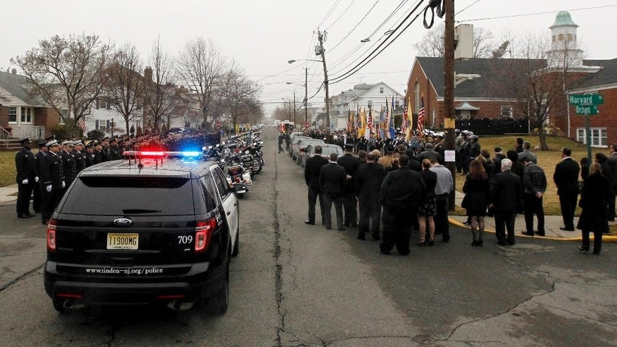 Officials and mourners gather outside of Linden Presbyterian Church before funeral services for Linden Officer Frank Viggiano, Thursday, March 26, 2015, in Linden, N.J.  Viggiano and Joseph Rodriguez died when the car they were riding in crashed head-on into a truck in the Staten Island borough of New York on Friday after a night at a strip club. Officers Pedro Abad Jr., who was driving the car, and Patrik Kudlac, remain hospitalized. The officers were off-duty at the time. (AP Photo/Julio Cortez)