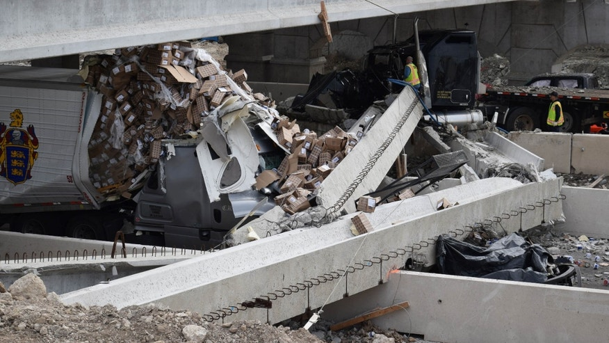 March 26, 2015: Authorities investigate a tractor-trailer that crashed into an overpass under construction.