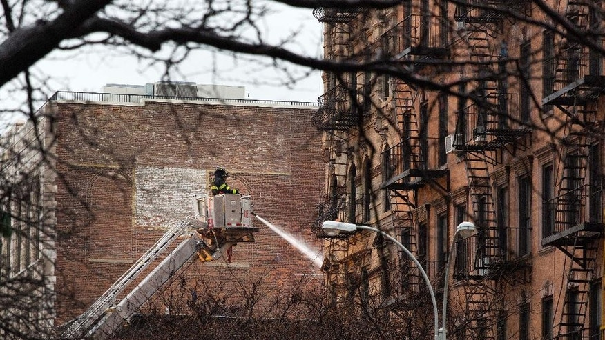 A firefighter directs water onto the site of an explosion and fire in the East Village neighborhood of New York, Friday, March 27, 2015. The powerful blast on Thursday caused the collapse of three buildings and fire damage to a fourth, the fire department said. It left four people in critical condition, more than a dozen others injured and one family searching for a loved one. Firefighters worked through the night to put out pockets. (AP Photo/Mark Lennihan)