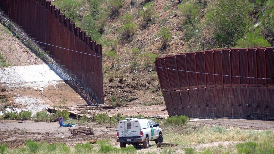 FILE - In this July 27, 2014, file photo, a border patrol vehicle stands guard at a section of collapsed fence just west of the Mariposa Port of Entry in Nogales, Ariz., after severe storms in southern Arizona over the weekend knocked down a chunk of the metal border fence that divides Mexico and the U.S. The federal government spent over $700,000 to repair part of a 60 feet of rebar-reinforced fencing in Nogales, Ariz., according to U.S. Customs and Border Protection documents released this month after a request by The Associated Press. (AP Photo/Nogales International, Jonathan Clark, File)