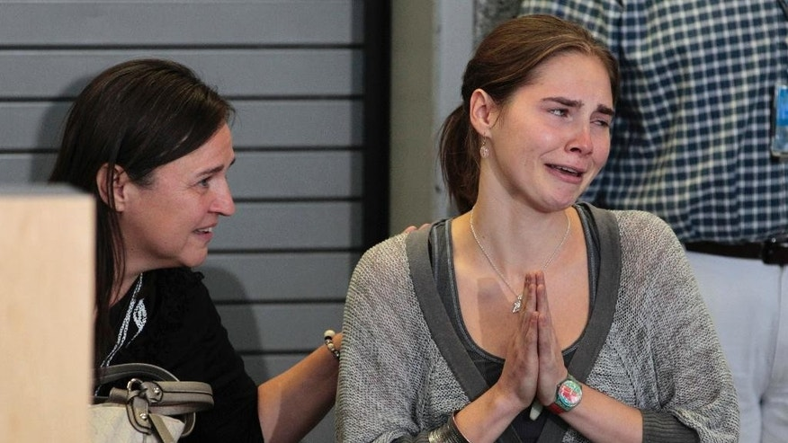 FILE -- In this Oct. 4, 2011 file photo Amanda Knox, flanked by her mother Edda Mellas, gestures at a news conference in Seattle, after returning home from Italy. American Amanda Knox and her Italian ex-boyfriend Raffaele Sollecito expect to learn their fate Friday when Italy's highest court hears their appeal of their guilty verdicts in the brutal 2007 murder of Knox's British roommate Meredith Kercher. Several outcomes are possible, including confirmation of the verdicts, a new appeals round, or even a ruling that amounts to an acquittal in the sensational case that has captivated audiences on both sides of the Atlantic. (AP Photo/Ted S. Warren)