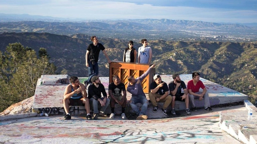 In this March, 2015 photo, members of a music video crew pose at Topanga Lookout in the Santa Monica Mountains with an upright piano they hauled up there in Calabasas, Calif. For a couple of days this week, a Southern California hilltop was alive with the sound of mystery.  Hikers venturing to Topanga Lookout found a battered upright piano sitting on a graffiti-scrawled concrete slab with a panoramic view over the mountains between Calabasas and the Pacific Ocean. Turns out, the piano was used for a music video by Seattle-based artist Rachel Wong. The cinematographer, Michael Flotron, says he and four others used a dolly and rope to haul the 350-pound instrument a mile up the trail on Tuesday. After the shoot, it was too dark to get the piano back down. Flotron says people seem happy to leave it there. But if necessary, he'll haul the piano back down.(AP Photo/Michael Flotron)