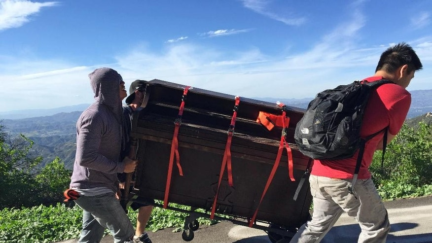 In this March, 2015 photo, members of a music video haul an upright piano to Topanga Lookout in the Santa Monica Mountains in Calabasas, Calif. For a couple of days this week, a Southern California hilltop was alive with the sound of mystery.  Hikers venturing to Topanga Lookout found a battered upright piano sitting on a graffiti-scrawled concrete slab with a panoramic view over the mountains between Calabasas and the Pacific Ocean. Turns out, the piano was used for a music video by Seattle-based artist Rachel Wong. The cinematographer, Michael Flotron, says he and four others used a dolly and rope to haul the 350-pound instrument a mile up the trail on Tuesday. After the shoot, it was too dark to get the piano back down. Flotron says people seem happy to leave it there. But if necessary, he'll haul the piano back down.(AP Photo/Michael Flotron)