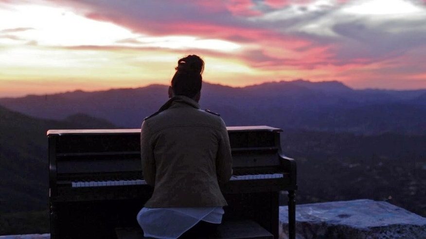 In this March, 2015 photo, a person sits at an upright piano that had been hauled up to Topanga Lookout in the Santa Monica Mountains in Calabasas, Calif. For a couple of days this week, a Southern California hilltop was alive with the sound of mystery.  Hikers venturing to Topanga Lookout found a battered upright piano sitting on a graffiti-scrawled concrete slab with a panoramic view over the mountains between Calabasas and the Pacific Ocean. Turns out, the piano was used for a music video by Seattle-based artist Rachel Wong. The cinematographer, Michael Flotron, says he and four others used a dolly and rope to haul the 350-pound instrument a mile up the trail on Tuesday. After the shoot, it was too dark to get the piano back down. Flotron says people seem happy to leave it there. But if necessary, he'll haul the piano back down.(AP Photo/Michael Flotron)