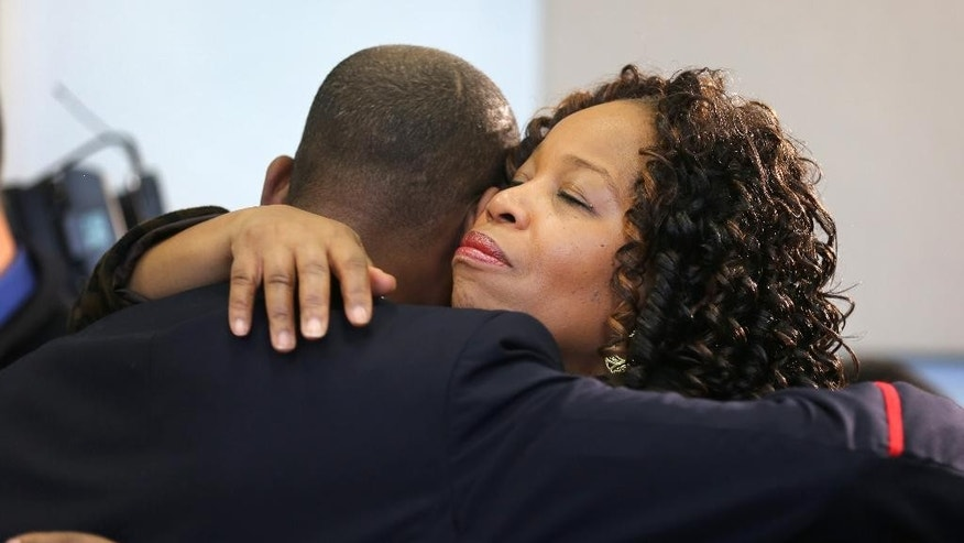 Ronnise Handy, CFO for the Cincinatti Fire Department, hugs Cincinnati District Chief Rafael Prophett, following a press conference at City Hall concerning the death of veteran Cincinnati firefighter Daryl Gordon, who died early Thursday, March 26, 2015 morning after falling down an elevator shaft at a 4-alarm fire in Cincinnati. Handy has known Gordon since their girls, now in college, were in 2nd grade.  (AP Photo/The Enquirer, Liz Dufour) NO SALES, MANDATORY CREDIT