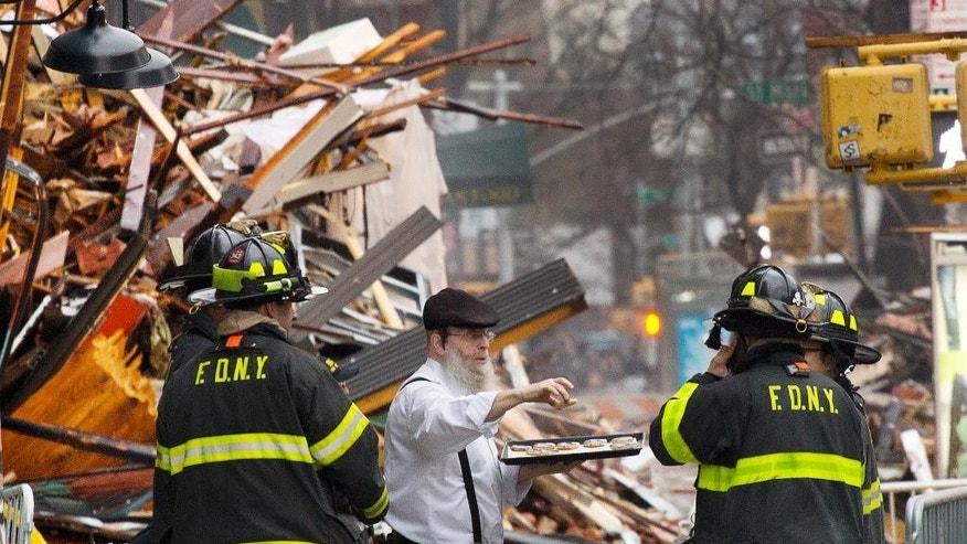 A man distributes pastries to weary firefighters at the site of an explosion and fire in the East Village neighborhood of New York, Friday, March 27, 2015. Thursday's inferno caused the collapse of three buildings and fire damage to a fourth, the fire department said. It left four people in critical condition and more than a dozen others injured and at least one family searching for a loved one. (AP Photo/Mark Lennihan)