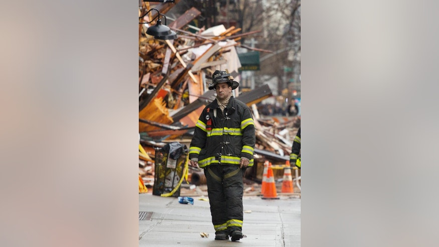 A firefighter walks away from a debris pile from collapsed buildings in the East Village neighborhood of New York, Friday, March 27, 2015. Authorities say two people are unaccounted for following an apparent gas explosion that leveled three buildings in the East Village neighborhood of New York. Preliminary evidence suggested a gas explosion amid plumbing and gas work inside the building was to blame.  (AP Photo/Mark Lennihan)
