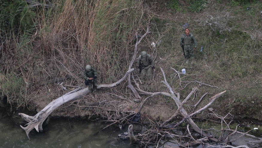 EDS NOTE: GRAPHIC CONTENT: In this Feb. 24, 2015 photo, Mexican officials examine a body, lower center in the water, discovered by the U.S. Customs and Border Protection Air and Marine while on patrol near the Texas-Mexico border, in Rio Grande City, Texas. Five bodies were found at the scene. Drowning deaths have spiked since last fall as a surge of law enforcement along the Mexico border prompts immigrants, desperate to avoid detection by a surge of law enforcement, to choose more dangerous and remote crossings into South Texas. (AP Photo/Eric Gay)